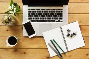 ノートパソコンと筆記用具の画像