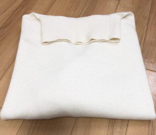 畳んだ白いニットの画像