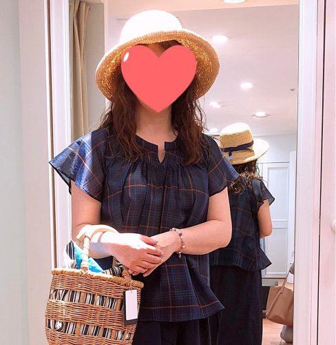 チェックのブラウスと麦わら帽子を試着する女性の画像