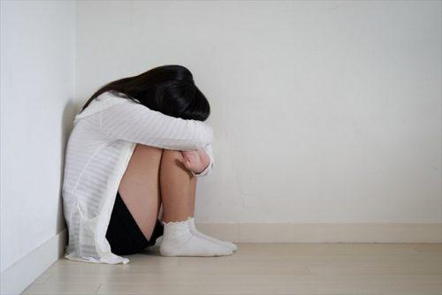 膝を抱える女子中学生の画像