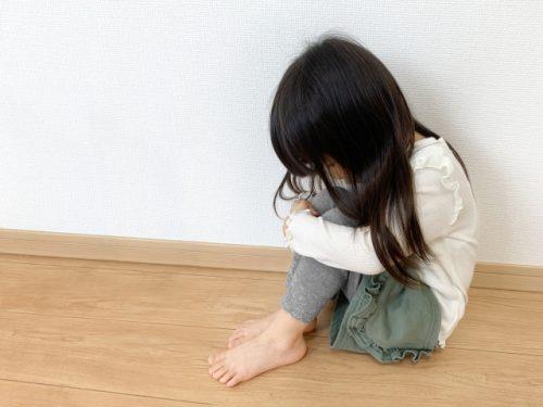 膝を抱え俯く女の子の画像