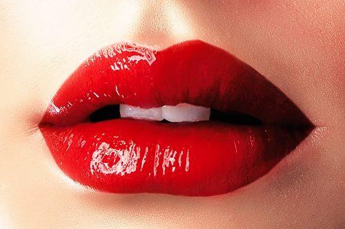真っ赤な口紅をする唇の画像