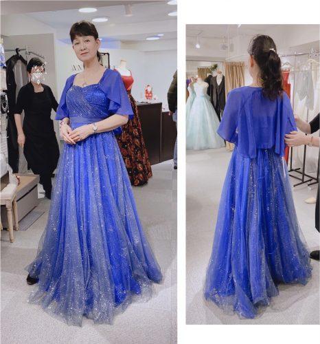 青いドレスを試着する女性の画像