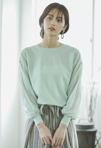 ミントグリーンのトップスを着る女性の画像